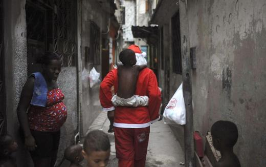 Leandro Wendell dos Santos, 14, wearing a Santa Claus costume, plays with kids as he walks along the alley of the Mare slum complex to distribute presents to children in Rio de Janeiro, Brazil, December 23, 2015. REUTERS/Fabio Teixeira