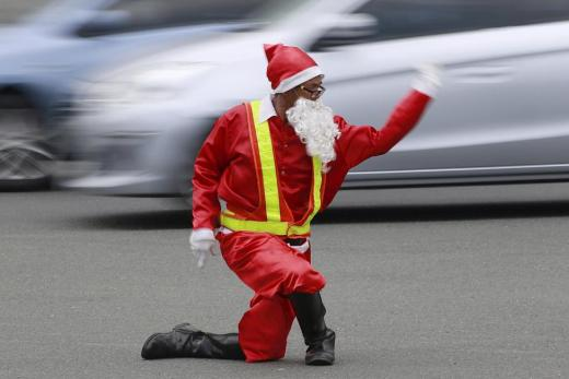 Traffic enforcer Ramiro Hinojas wears a Santa Claus costume while directing traffic flow at a busy intersection in Pasay city, metro Manila, December 12, 2015. Hinojas busts some dance moves while directing traffic to entertain motorists stuck in the congested intersection as holiday-goers crowd malls for their yuletide shopping a few days before Christmas. REUTERS/Romeo Ranoco