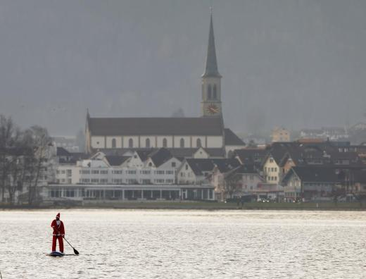 A man dressed as Santa Claus on a stand-up paddle crosses Lake Aegerisee near Unteraegeri, Switzerland December 5, 2015. REUTERS/Arnd Wiegmann