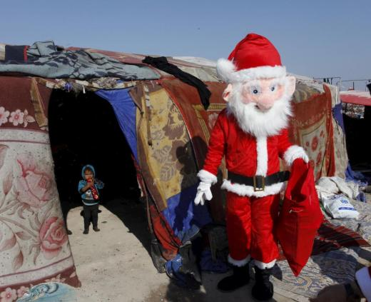A volunteer wearing a Santa Claus costume distributes presents to children at a poor community in Najaf, south of Baghdad, December 19, 2015.  REUTERS/Alaa Al-Marjani