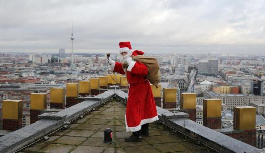 A man dressed as a Santa Claus poses on top of the Kollhoff Tower at Potsdamer Platz square in Berlin, Germany, December 13, 2015 REUTERS/Fabrizio Bensch