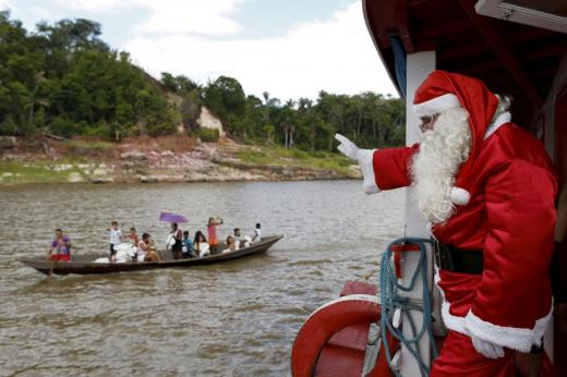 Claudionor Jose de Deus, wearing a Santa Claus costume, waves to people on a boat in the Amazon River, in rural Manaus, Brazil, December 19, 2015. Jose de Deus is part of a volunteer group that distributes toys to children from poor neighborhoods and riverside communities that are distant from the city. REUTERS/Bruno Kelly