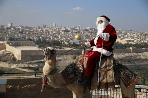 Israeli-Arab Issa Kassissieh wears a Santa Claus costume as he rides a camel and poses for the media during an annual Christmas tree distribution by the Jerusalem municipality on the Mount of Olives in Jerusalem, December 21, 2015. The Dome of the Rock is seen in the background. REUTERS/Ammar Awad