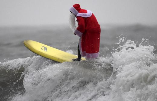 A member of the Langland Board Surfers group takes part in a Surfing Santa competition at Langland Bay in Gower, Wales, December 19, 2015. REUTERS/Rebecca Naden